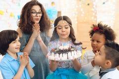 La niña hermosa con el tocado en la cabeza sopla hacia fuera velas en la torta de cumpleaños Partido del feliz cumpleaños imágenes de archivo libres de regalías
