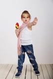 La niña hermosa con la piruleta con la mano pintada de la parada de la demostración de la cara en niños ama concepto del dulce y  Fotografía de archivo