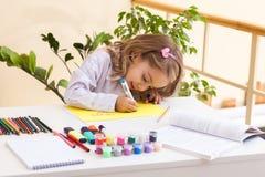 La niña hermosa dibuja sentarse en la tabla Fotografía de archivo