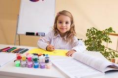 La niña hermosa dibuja sentarse en la tabla Foto de archivo