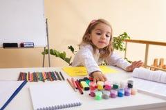 La niña hermosa dibuja sentarse en la tabla Imágenes de archivo libres de regalías