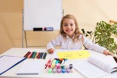 La niña hermosa dibuja sentarse en la tabla Imagen de archivo