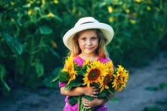 La niña hermosa en el sombrero brimmed ancho blanco con el girasol florece en el campo Fotos de archivo