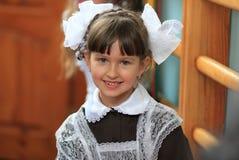 La niña hermosa en un vestido y arcos de la escuela Foto de archivo