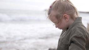 La niña hermosa en una chaqueta mira el mar almacen de video