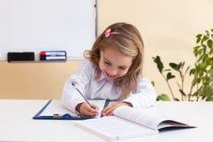 La niña hermosa escribe sentarse en la tabla Imágenes de archivo libres de regalías