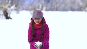 La niña hermosa está jugando en el campo en la nieve Tenga nieve que lanza de la diversión para arriba almacen de metraje de vídeo