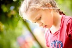 La niña hermosa examina cuidadosamente sus zapatos al aire libre en a foto de archivo libre de regalías