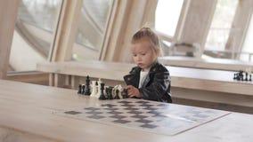 La niña hermosa juega con los pedazos de ajedrez almacen de metraje de vídeo