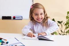 La niña hermosa lee sentarse en la tabla Foto de archivo libre de regalías
