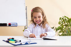 La niña hermosa lee sentarse en la tabla Foto de archivo