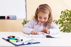 La niña hermosa lee sentarse en la tabla Imagen de archivo libre de regalías