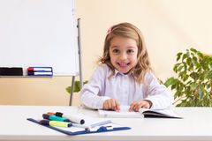 La niña hermosa lee sentarse en la tabla Fotos de archivo libres de regalías