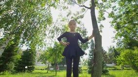 La niña hermosa que hace la gimnasia ejercita en la hierba en el verano almacen de video