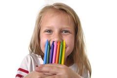 La niña hermosa que sostenía los creyones multicolores fijó en concepto de la educación de los alumnos del arte Fotografía de archivo libre de regalías