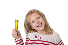 La niña hermosa que sostenía los creyones multicolores fijó en concepto de la educación de los alumnos del arte Imagenes de archivo