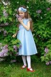 La niña hermosa se está colocando en los arbustos de una lila Imagen de archivo