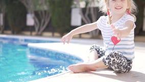 La niña hermosa toca el agua de la mano en la piscina metrajes