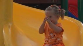La niña hermosa va para una impulsión en una colina de los niños ella aplaude sus manos almacen de metraje de vídeo