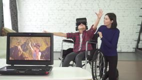 La niña inhabilitó en un casco de la silla de ruedas y del vr, riendo, usando la tecnología 3d almacen de video