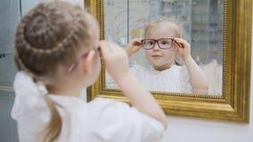 La niña intenta el espejo cercano de los nuevos vidrios - compras en clínica de la oftalmología imagenes de archivo