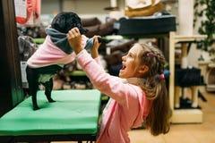 La niña intenta encendido la ropa para el perrito en la tienda de animales Imagen de archivo