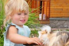 La niña introduce el conejillo de Indias en patio Foto de archivo libre de regalías