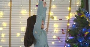 La niña juega con confeti y se divierte que salta en sala de estar almacen de video