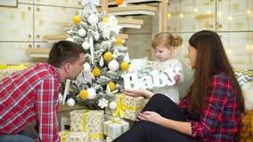 La niña juega con el bebé de madera de la palabra cerca de padres en el tiempo de la Navidad en casa almacen de metraje de vídeo