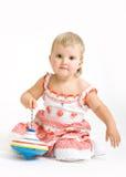 La niña juega con el juguete en el fondo blanco Imágenes de archivo libres de regalías