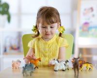 La niña juega con pocos animales del juguete mientras que se sienta en la tabla foto de archivo