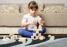 La niña juega los cubos de madera del juguete Imagen de archivo
