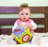 La niña juega a un bebé del juguete en la cama Fotografía de archivo