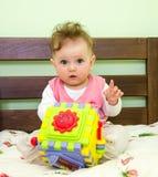 La niña juega a un bebé del juguete en la cama Imagenes de archivo
