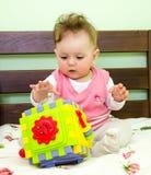 La niña juega a un bebé del juguete en la cama Imagen de archivo