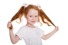 La niña juguetona sostiene el pelo de las manos Fotos de archivo