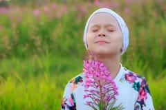 La niña la cerró los ojos y respira el aire fresco en el parque fotografía de archivo