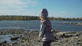 La niña lanza piedras en el río almacen de metraje de vídeo