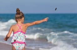 La niña lanza rocas en el mar imagenes de archivo