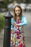 La niña lava las manos debajo de la bomba de mano del agua en la calle en la ciudad vieja Foto de archivo