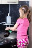 La niña lava platos con la esponja imagenes de archivo