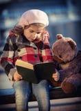 La niña lee el libro imagenes de archivo