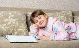 La niña lee el libro que miente en un sofá Fotografía de archivo