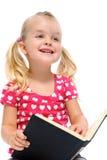 La niña lee el libro y sonríe Fotos de archivo