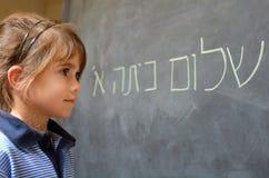 La niña lee hola saludos del primer grado en hebreo Foto de archivo