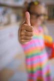 La niña levanta los pulgares para arriba Imagen de archivo libre de regalías