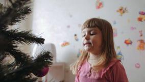 La niña linda adorna el árbol de navidad metrajes