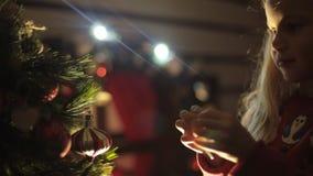 La niña linda adorna el árbol de navidad para almacen de metraje de vídeo