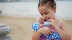 La niña linda alimenta su muñeca preferida de una botella del juguete Poco niño que juega con la muñeca en el parque por el mar F almacen de metraje de vídeo