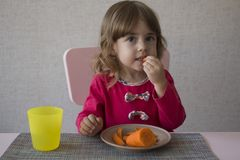 La niña linda come la zanahoria Imagen de archivo